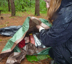 Temporary shelter for injured person in a wilderness setting
